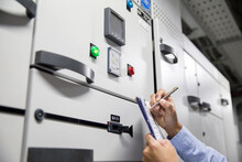 Electrical Engineer Checking Electric Current Voltage At Breaker Of Air Handling Unit (AHU) Starter Control Panel For Air Conditioner Or Load Center Cabinet For Maintenance In Main Power Distribution.