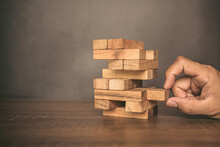 Close-up Hand Pull Wooden Block From Other The Wood Block Stacked In Tower Shape Concepts Of Financial Risk Management And Strategic Planning.
