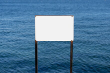 During Sunny Bright Day Time Blank White Board In Front Of The Blue Sea