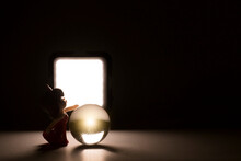 Silhouette Cute Girl Doll Touching Crystal Ball On Dark Background.