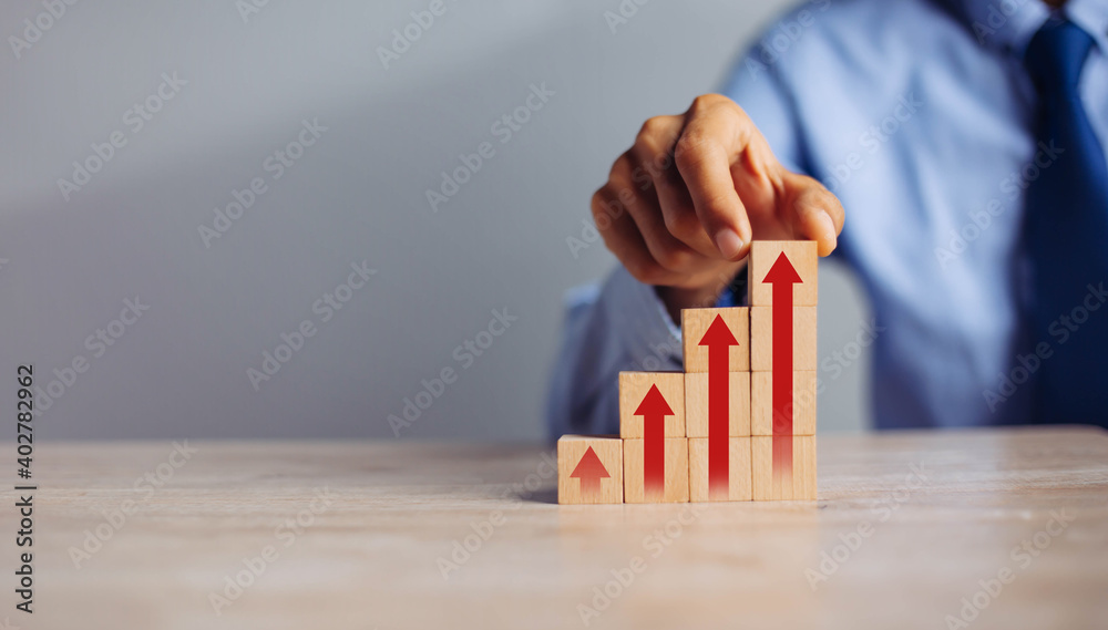 Fototapeta businessman hand  arranging wood block stacking as step stair with arrow up.concept for business growth success process.
