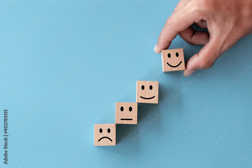 Fototapeta Close up top view customer hand choose smiley face on wood cube, Service rating, satisfaction concept.