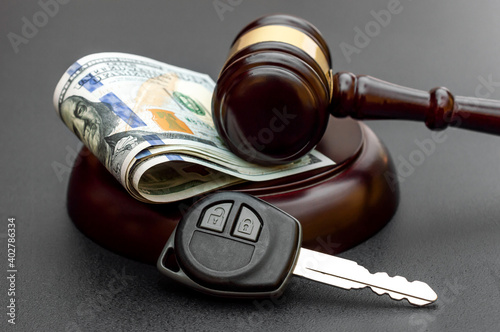 Obraz Judge's gavel with car key and money on black. - fototapety do salonu