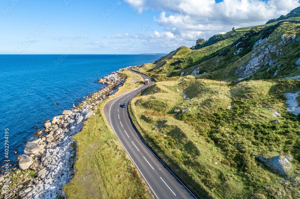 Fototapeta Causeway Costal Route with cars, a.k.a. Antrim Coastal Road on eastern coast of Northern Ireland, UK.