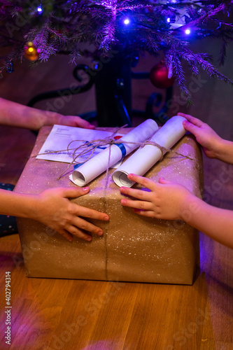 wrapped present under a christmas tree in children's hands at home. little sibling kids give each other gifts. new year homemade holiday gifts box wrapped on craft paper. noisy and grain effect Wall mural