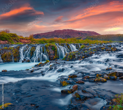 Beautiful summer scenery of Bruarfoss Waterfall, secluded spot with cascading blue waters. Magnificent sunset in Iceland, Europe. Landscape photography..
