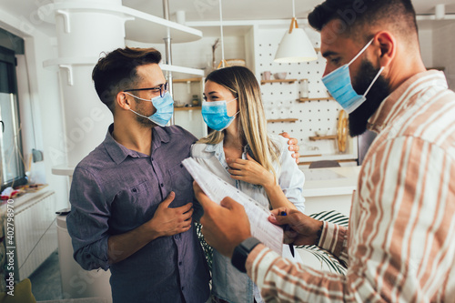 Young happy married couple in medical masks standing in the new house with male real-estate agent. Pandemic concept.