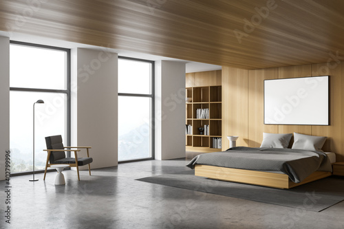 Fotografering White and wooden master bedroom corner with poster and armchair