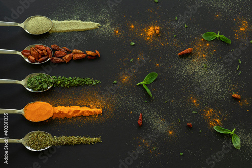 Foto Cucharas con especias, pimienta, gindillas, oreganosobre mesa color oscuro