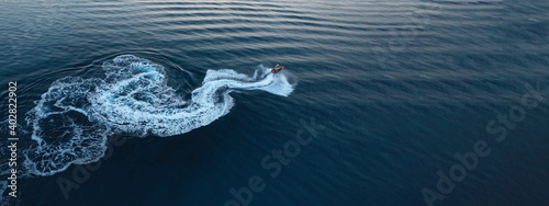 Obraz Aerial drone ultra wide photo of jet ski watercraft performing extreme manoeuvres in deep blue bay with calm sea at dusk - fototapety do salonu