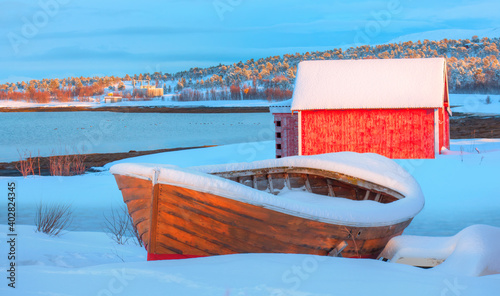Canvastavla Beautiful winter landscape with old fishing red cabin (boathouse) boat at sunset