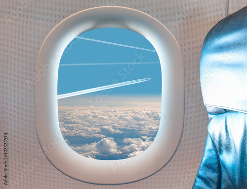 Obraz Heavy traffic in the sky - Trail of white smoke from the airplane on blue sky as seen through window of an aircraft - fototapety do salonu