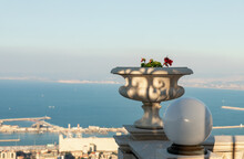A Large Stone Decorative Pot With Geraniums And A White Lantern On The Upper Terrace Of The Bahai Garden Against The Backdrop Of The Downtown And The Mediterranean Sea In The Rays Of The Setting Sun I