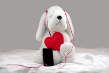White Plush Dog Toy Listening To Music On Headphones With Red Heart.