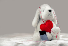 White Plush Dog Toy Listening To Music On Headphones With Red Heart, Copy Space.
