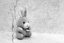 Toy Soft Rabbit On The Background Of Plaster, Black And White Image