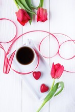 Red Tulips, Black Coffee And Candy Hearts On A White Background