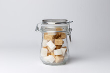 Jar With White Sugar Cubes And Brown Cane Sugar Lump On White Background. Dry Food Product On Home Kitchen