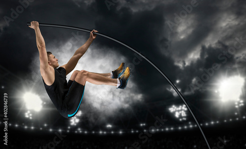 Professional pole vaulter training at the stadium in the evening - fototapety na wymiar