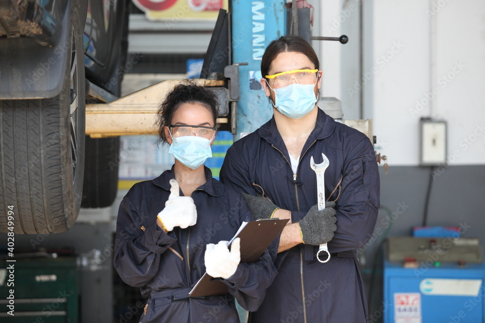 Fototapeta two car mechanic on protective mask anti coronavirus and they are fixing car engine in garage