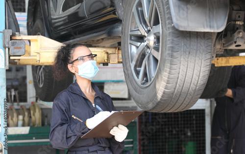 Obraz car mechanic on protective mask anti coronavirus and they are fixing car engine in garage - fototapety do salonu