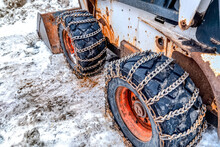 Old And Rusty Bulldozer With Heavy Duty Black Wheels Wrapped In Metal Chains