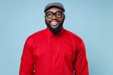 Cheerful Smiling Attractive Young Bearded African American Man 20s Wearing Casual Red Shirt Cap Eyeglasses Standing And Looking Camera Isolated On Pastel Blue Color Wall Background Studio Portrait.