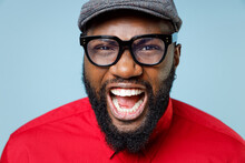 Close Up Of Crazy Screaming Young Bearded African American Man 20s Wearing Casual Red Shirt Cap Eyeglasses Standing And Looking Camera Isolated On Pastel Blue Color Wall Background Studio Portrait.