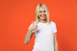 canvas print picture - Smiling cheerful elderly gray-haired blonde woman lady 40s 50s years old in white casual t-shirt standing showing thumb up looking camera isolated on bright orange color background studio portrait.