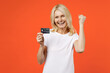 canvas print picture - Happy elderly gray-haired blonde woman lady 40s 50s years old wearing white basic t-shirt hold credit bank card doing winner gesture looking camera isolated on orange color background studio portrait.