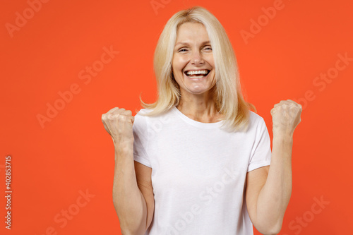 Foto Funny joyful elderly gray-haired blonde woman lady 40s 50s years old in white casual t-shirt standing doing winner gesture clenching fists isolated on bright orange color background studio portrait