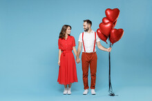 Full Length Of Smiling Young Couple Friends Man Woman In White Red Clothes Celebrating Birthday Holiday Party Hold Bunch Of Air Inflated Helium Balloons Holding Hands Isolated On Blue Background.