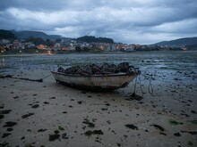 Stranded Beached Fishing Boat Vessle Ship On Coastline Shore Of Seaside Town Village Combarro Galicia Spain At Low Tide