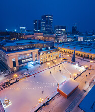 Aerial View Of People Having Fun And Skating On The Ice Rink On The Background Of A Christmas Tree Decorated For The New Year In A Fabulous Winter City Near Shopping Mall