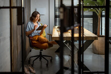 Creative Woman Working On A Touchpad At The Cozy And Stylish Home Office. Full Shot