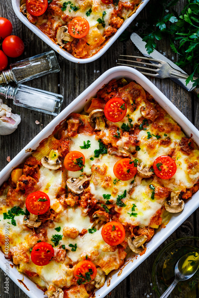 Fototapeta Noodle casserole with minced meat, mozzarella cheese and vegetables on wooden table