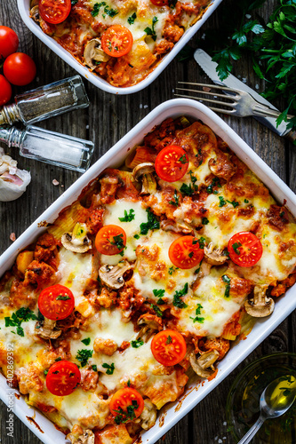 Photo Noodle casserole with minced meat, mozzarella cheese and vegetables on wooden ta