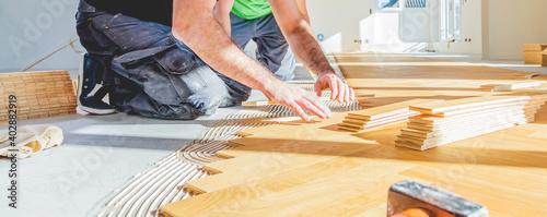 Obraz worker installing oak herringbone parquet floor during home improvement - fototapety do salonu