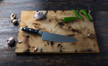 Wooden Board With Natural Ingredients Such As Garlic, Ginger And Serrano Pepper With Stainless Steel Knife.