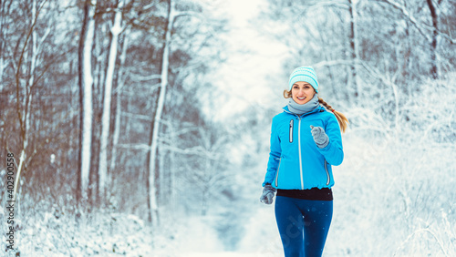 Fototapeta Woman jogging towards camera in cold and snowy forest obraz