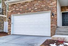 White Garage Door Adjacent To Stairs Going Up To The Front Door Door Of House