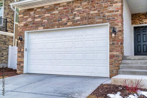 White garage door adjacent to stairs going up to the front door door of house Wallpaper Mural