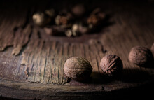 Still Life With Walnut Kernels And Whole Walnuts On Rustic Old Wooden Table. Creative Table Decoration.