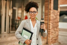 Young African American Businesswoman Holding Bottle Of Water At The City.