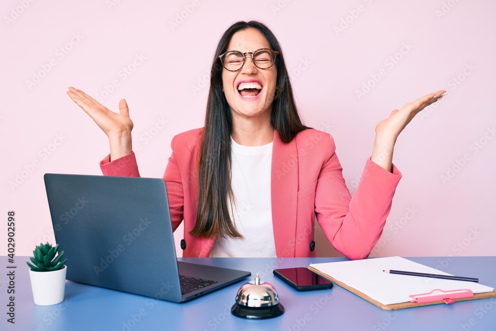 Fototapeta Young caucasian woman sitting at the recepcionist desk working using laptop celebrating mad and crazy for success with arms raised and closed eyes screaming excited. winner concept