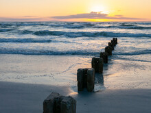 Ruins Of An Old Pier On The Right Side With A Wide View Of The Sunset On Siesta Key Beach And Blue Waves.