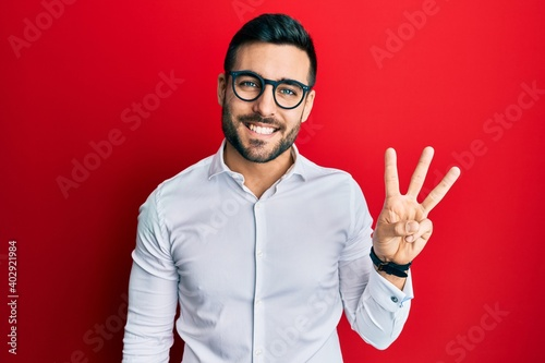 Fotografia, Obraz Young hispanic businessman wearing shirt and glasses showing and pointing up with fingers number three while smiling confident and happy