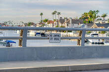 No Jumping Off Bridge Sign Against Huntington Beach Harbor With Boats And Docks
