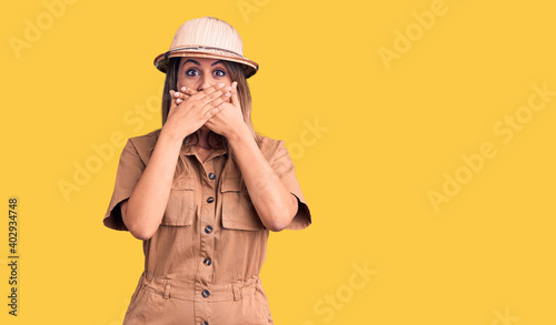 Fotografia Young beautiful woman wearing explorer hat shocked covering mouth with hands for mistake