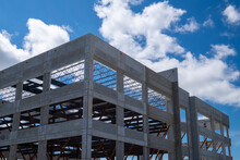 A Large Multiple Storey Precast Grey Concrete Building With Steel Beams Against A Blue Sky. The Industrial Structure Is The Corner Of A Skyscraper Building With Prefabricated Engineering Formwork.